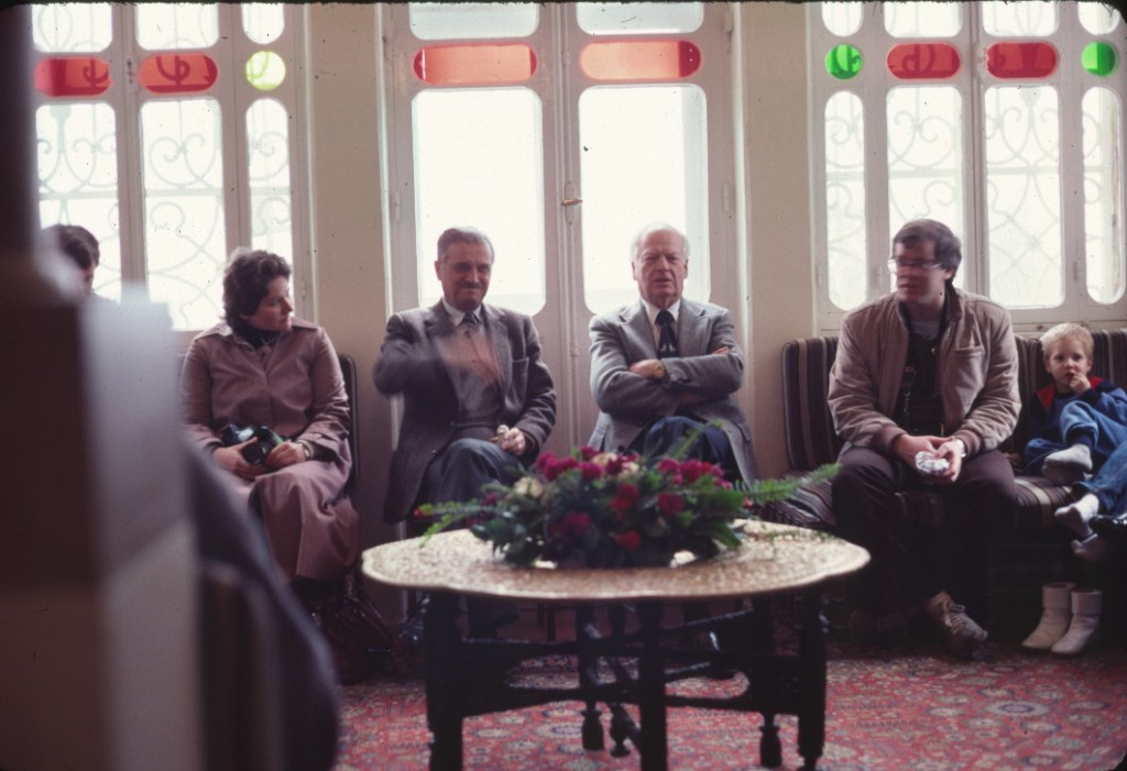Mr. 'Alí Nakhjavání and Mr. Charles Wolcott, members of the Universal House of Justice, meet with pilgrims in the Pilgrim House in 1983.